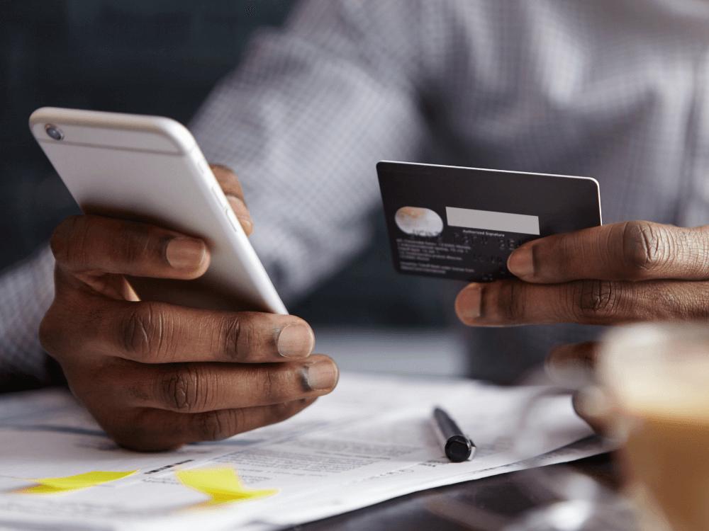 mãos negras segurando iPhone e cartão de crédito para fazer pagamento online
