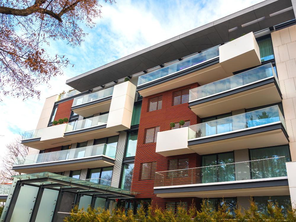 Prédio residencial moderno com fachada nas cores bege e vinho e vidraças longas. Dia de Sol com nuvens ao fundo