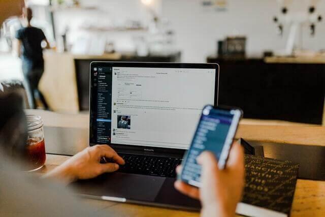 Design em Loja Virtual: a importância de otimizar para smartphone: homem olhando celular na frente de um computador