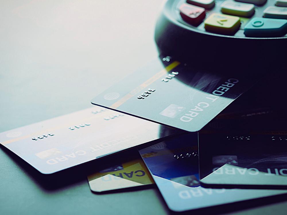 retentativa com troca de adquirente: imagem parcial de uma máquina de cartão de crédito com 1 cartão inserido e outros 4 ao redor de uma mesa cinza