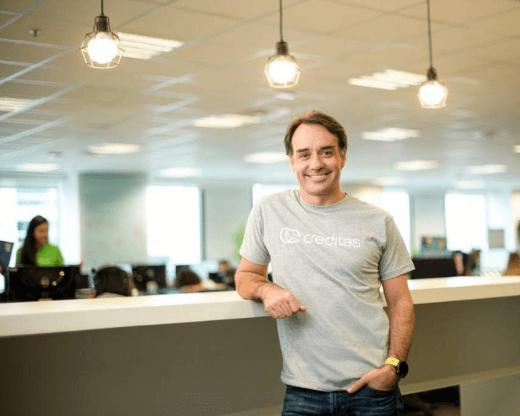 Imagem de Sergio Furio, CEO da Creditas (homem branco com camiseta cinza) apoiado na bancada do escritório da Creditas