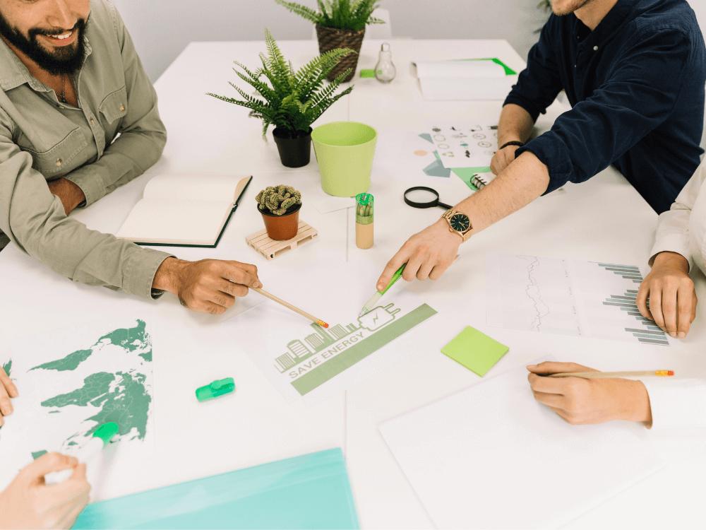 ESG - imagem de pessoas de negócios em volta de mesa branca apontando para papel com texto save energy