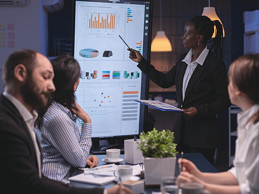 Vindi Insights Agosto 2021 - imagem de pessoas de negócios diversas olhando para tela com dados e mulher negra apresentando