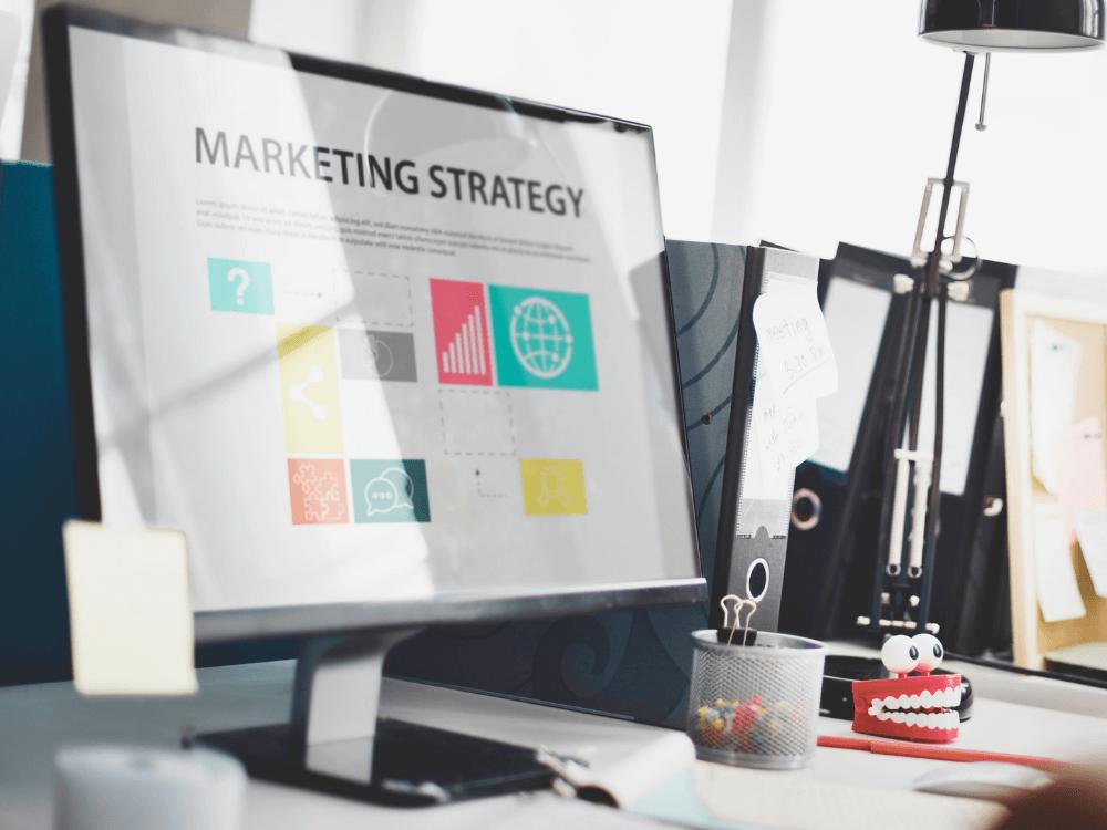 Nomes para Loja Virtual - imagem de um computador em mesa executiva e texto Marketing Strategy na tela